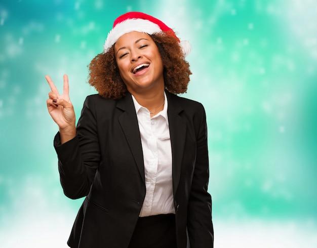 Jovem, negócio, mulher preta, desgastar, um, chirstmas, chapéu santa, fazendo um gesto, de, vitória