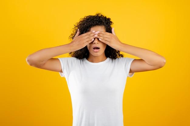 Jovem negra africana, cobrindo os olhos com as mãos isoladas sobre amarelo