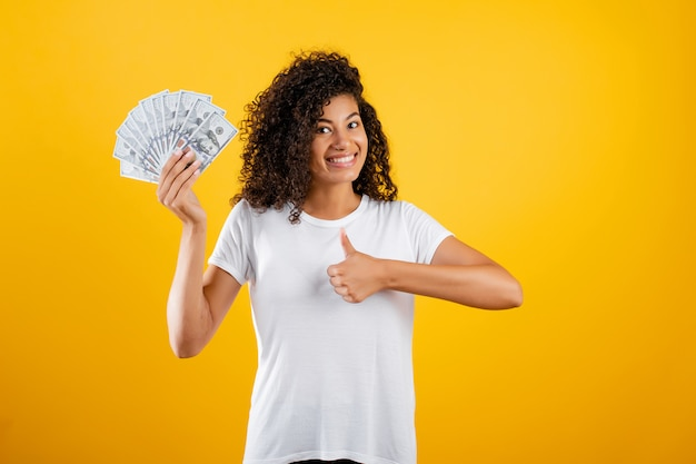 Jovem negra africana com dinheiro dólares na mão isolado sobre amarelo
