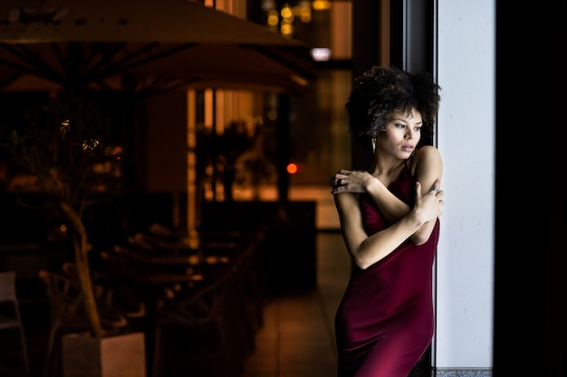 Jovem negra afro-americana à noite na rua. mulher posando perto da janela de um café de rua, vestida com um lindo vestido vermelho. conceito de vida noturna, moda e estilo