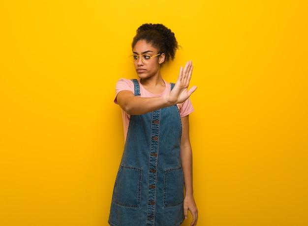 Jovem negra afro-americana com olhos azuis colocando a mão na frente