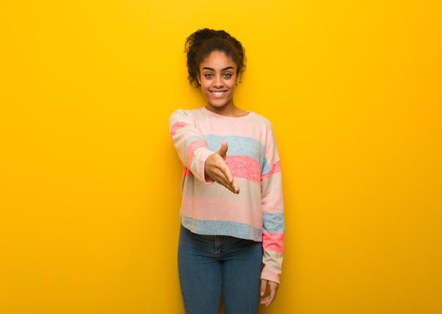 Jovem negra afro-americana com olhos azuis estendendo a mão para cumprimentar alguém