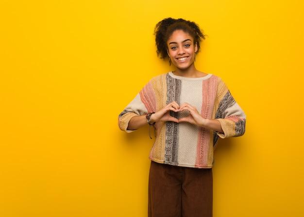 Jovem negra afro-americana com olhos azuis fazendo um formato de coração com as mãos