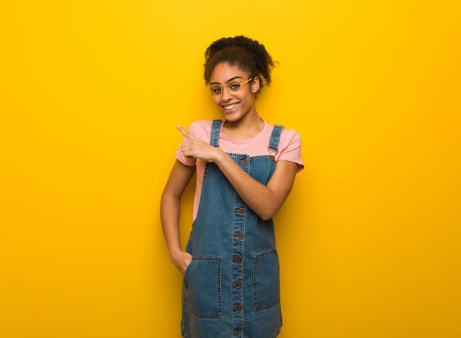 jovem negra afro-americana com olhos azuis sorrindo e apontando para o lado