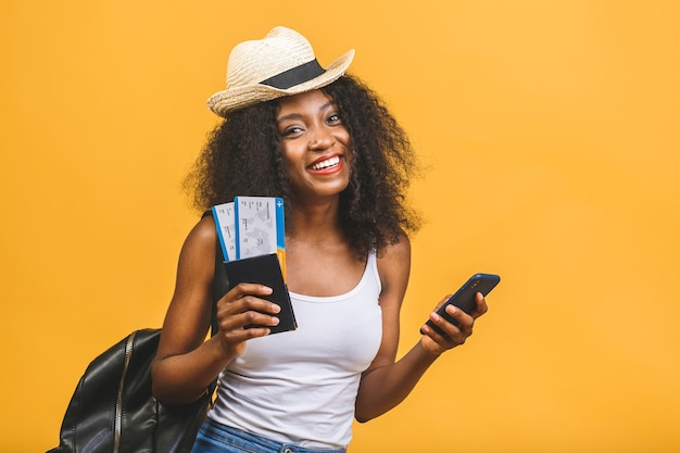 Jovem negra afro-americana feliz com passagens aéreas usando o telefone