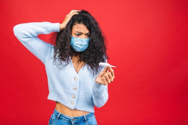 Jovem negra afro-americana preocupada usando máscara médica isolada sobre fundo vermelho