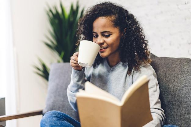Jovem negra afro-americana relaxante bebendo uma xícara de café ou chá quente e lendo o livro no sofá em casa