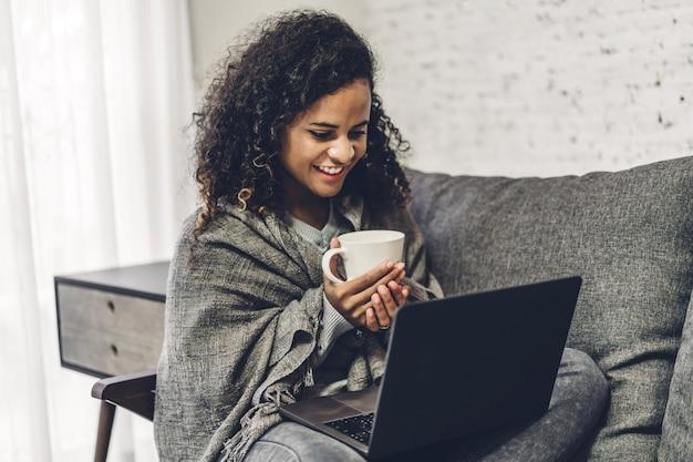 Jovem negra afro-americana relaxante e usando o computador portátil. mulher, verificação de aplicativos sociais e trabalho. conceito de comunicação e tecnologia