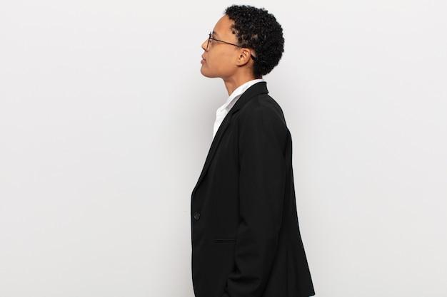 Jovem negra afro em vista de perfil, olhando para copiar o espaço à frente, pensando, imaginando ou sonhando acordada