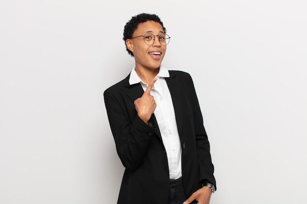 Jovem negra afro parecendo animada e surpresa, apontando para o lado e para cima para copiar o espaço