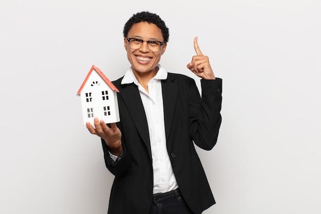 Jovem negra afro se sentindo um gênio feliz e animado depois de realizar uma ideia, levantando o dedo alegremente, eureka!