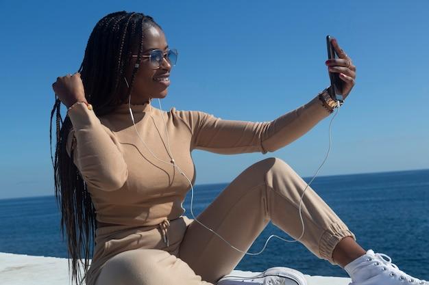 Jovem negra afro sorrindo olhando para o celular dela, ao ar livre com o céu azul e o fundo do mar. tecnologia, comunicação, redes sociais.