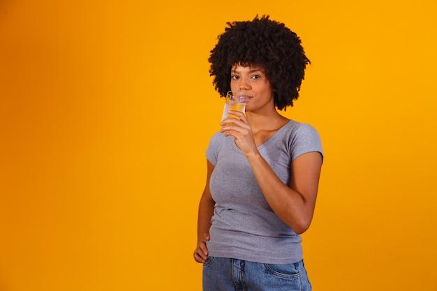 Jovem negra água potável em amarelo. jovem com um copo de água