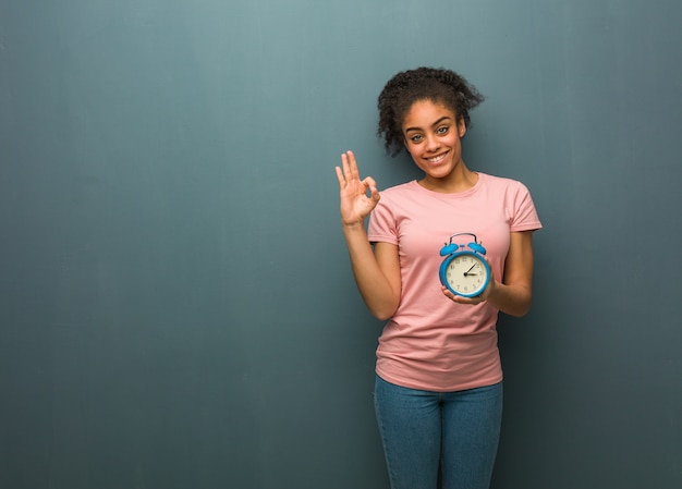 Jovem negra alegre e confiante fazendo gesto de ok. ela está segurando um despertador.