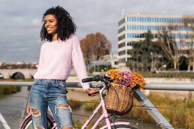 Jovem negra andando de bicicleta vintage