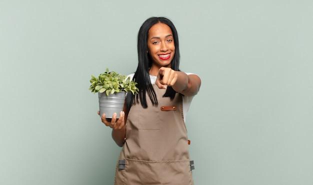 Jovem negra apontando com um sorriso satisfeito, confiante e amigável, escolhendo você. conceito de jardineiro