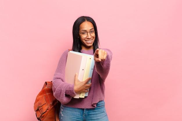 Jovem negra apontando para a câmera com um sorriso satisfeito, confiante e amigável, escolhendo você. conceito de estudante