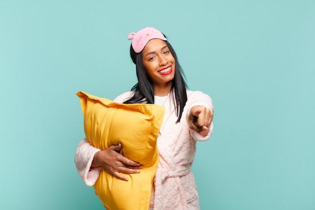 Jovem negra apontando para a câmera com um sorriso satisfeito, confiante e amigável, escolhendo você. conceito de pijama