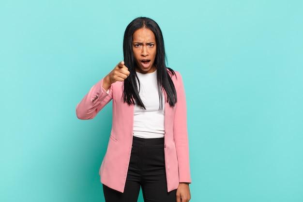 Jovem negra apontando para a câmera com uma expressão agressiva e zangada, parecendo um chefe louco e furioso. conceito de negócios