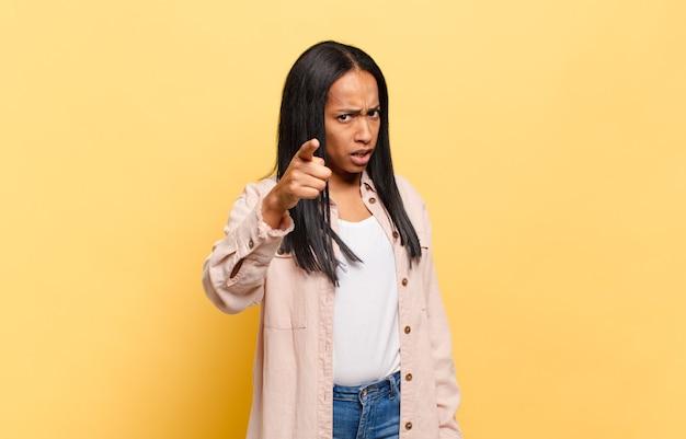 Jovem negra apontando para a câmera com uma expressão agressiva e zangada, parecendo um chefe louco e furioso