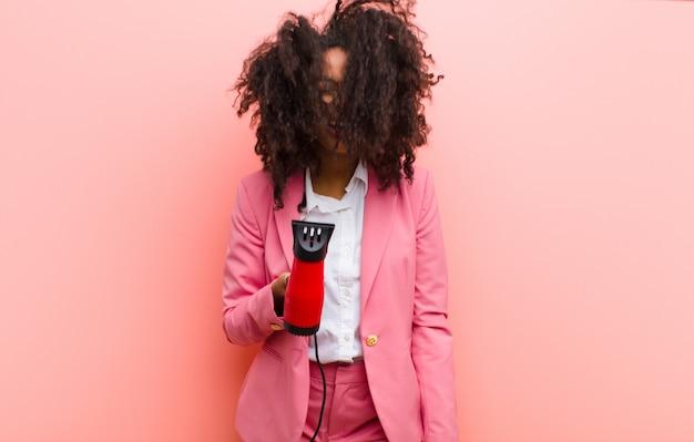 Jovem negra bonita com um cabeleireiro contra uma parede rosa
