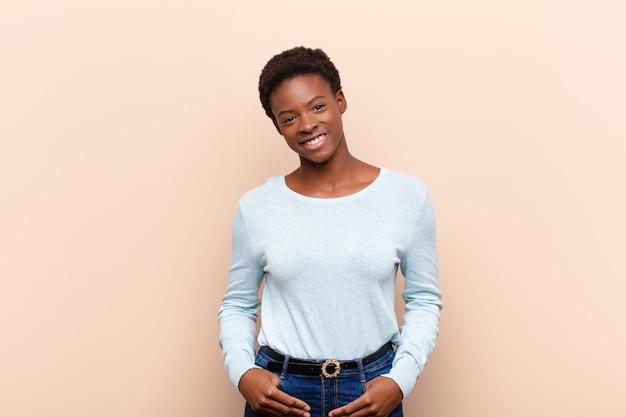 Jovem negra bonita sorrindo alegre e casualmente com uma expressão positiva, feliz, confiante e relaxada