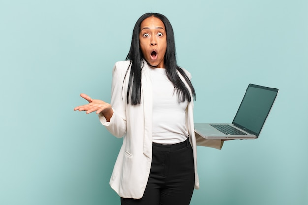 Jovem negra boquiaberta e pasma, chocada e atônita com uma surpresa inacreditável. conceito de laptop