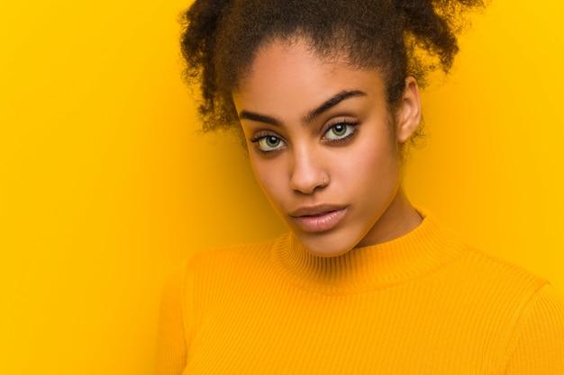 Jovem negra closeup sobre uma parede laranja