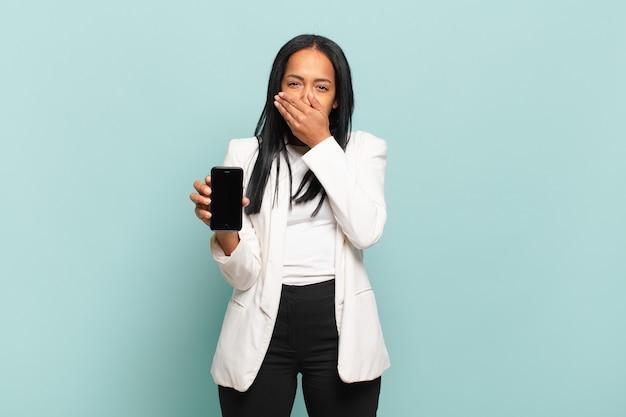 Jovem negra cobrindo a boca com as mãos com uma expressão chocada e surpresa, mantendo um segredo ou dizendo oops. conceito de telefone inteligente