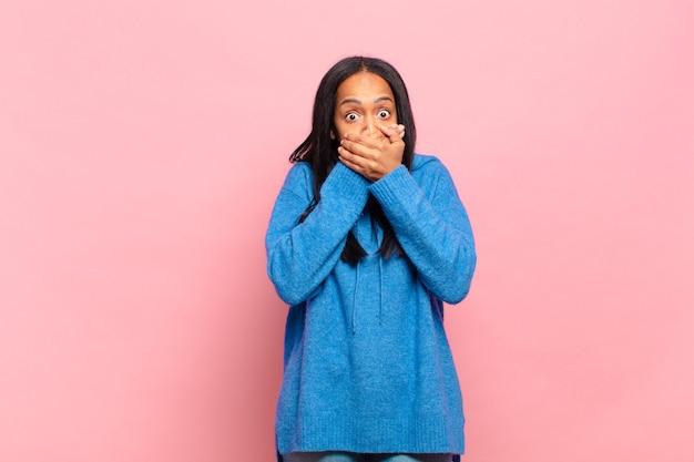 Jovem negra cobrindo a boca com as mãos com uma expressão chocada e surpresa, mantendo um segredo ou dizendo oops