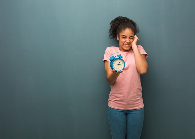 Jovem negra cobrindo as orelhas com as mãos. ela está segurando um despertador.