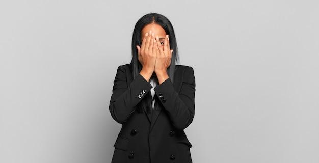 Jovem negra cobrindo o rosto com as mãos, espiando por entre os dedos com expressão de surpresa e olhando para o lado. conceito de negócios