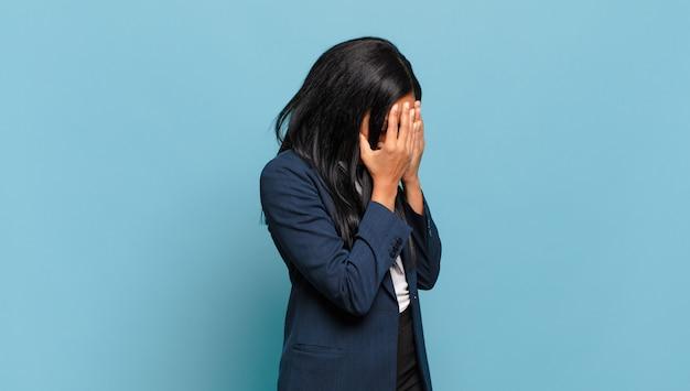 Jovem negra cobrindo os olhos com as mãos com um olhar triste e frustrado de desespero, chorando, vista lateral. conceito de negócios