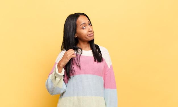 Jovem negra com ar arrogante, bem-sucedida, positiva e orgulhosa, apontando para si mesma