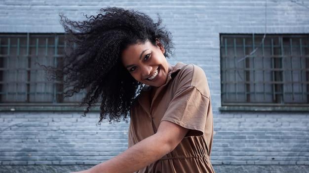 Jovem negra com cabelo afro, rindo e curtindo