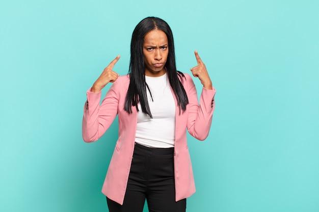 Jovem negra com uma atitude ruim, parecendo orgulhosa e agressiva, apontando para cima ou fazendo sinal divertido com as mãos. conceito de negócios