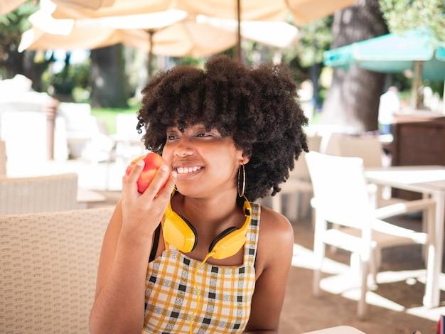 Jovem negra comendo uma maçã vermelha fresca enquanto está sentada em uma cafeteria, ao ar livre