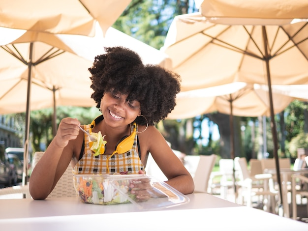Jovem negra comendo uma salada fresca do lado de fora, em uma cafeteria
