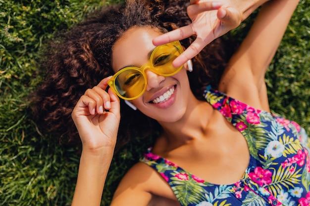 Jovem negra elegante ouvindo música em fones de ouvido sem fio, se divertindo deitado na grama, no parque, estilo de moda de verão, roupa colorida hipster, vista de cima