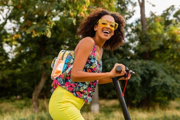 Jovem negra elegante se divertindo no parque, andando de scooter elétrica no estilo da moda de verão, roupa colorida hipster, usando mochila e óculos de sol amarelos