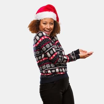 Jovem negra em uma camisola de natal na moda com impressão segurando algo com as mãos
