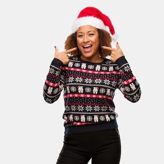 Jovem negra em uma camisola de natal na moda com sorrisos de impressão, apontando a boca