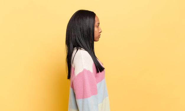 Jovem negra em vista de perfil, olhando para copiar o espaço à frente, pensando, imaginando ou sonhando acordada