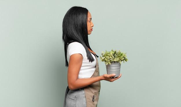 Jovem negra em vista de perfil, olhando para copiar o espaço à frente, pensando, imaginando ou sonhando acordado. conceito de jardineiro
