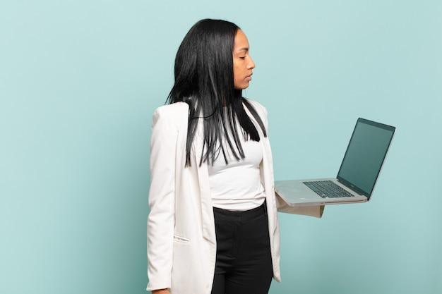 Jovem negra em vista de perfil, olhando para copiar o espaço à frente, pensando, imaginando ou sonhando acordado. conceito de laptop