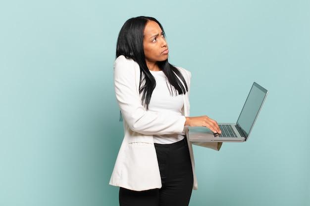 Jovem negra encolhendo os ombros, sentindo-se confusa e insegura, duvidando com os braços cruzados e olhar perplexo. conceito de laptop