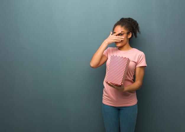 Jovem negra envergonhada e rindo ao mesmo tempo. ela está segurando um balde de pipoca.