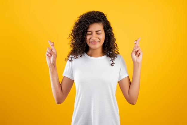 Jovem negra esperando e rezando com os dedos cruzados isolados sobre amarelo