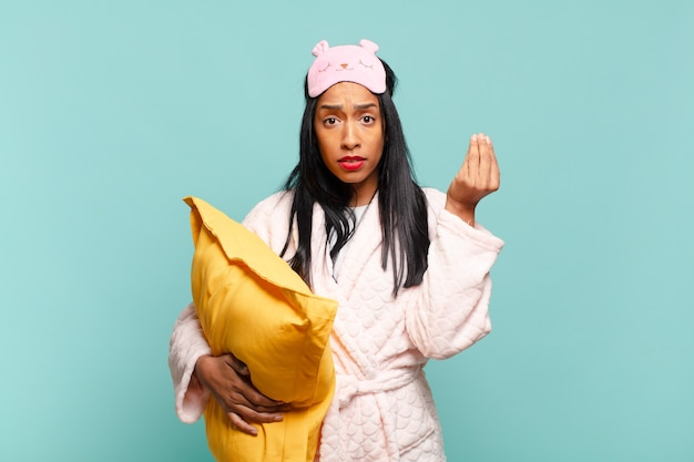 Jovem negra fazendo capice ou gesto de dinheiro, mandando você pagar suas dívidas !. conceito de pijama