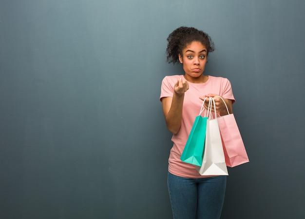 Jovem negra, fazendo um gesto de necessidade. ela está segurando uma sacola de compras.